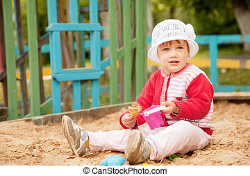two-year child playing with sand