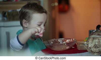 Two year old boy is eating fish soup from the plate. Clip three.