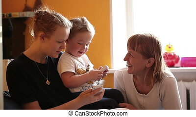 Two year-old boy plays with his mother and grandmother.