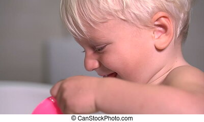 two year old boy trying to rinse his mouth after brushing his teeth, close up