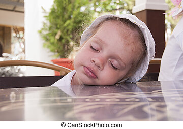 Two-year-old girl asleep at a table