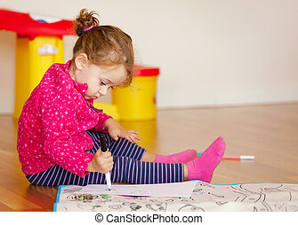 Two-year-old girl draws and colors on the floor.