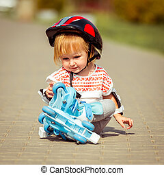 two year old  girl in roller skates and a helmet