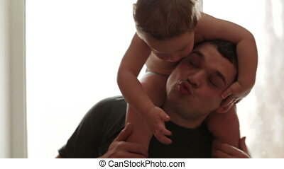 Two year old son is sitting on the father's shoulders.
