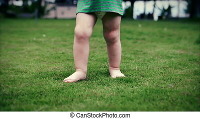 Two-year-old toddler little boy walks on the summer of on the green grass. Slow motion. Clouse up.