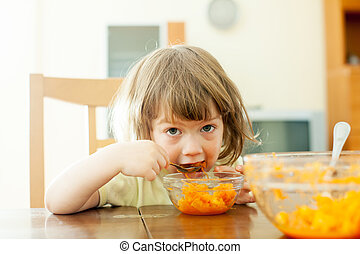 Two years child eats carrot salad in home