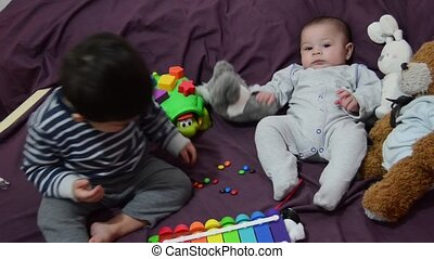 two years old and 4 months old boys playing on purrple ...