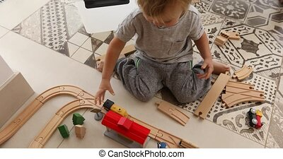 Two years old boy plays with wooden railroad