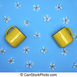 two yellow ceramic mugs on a blue background