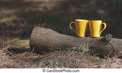 Two yellow cups on the log. Background for web site.