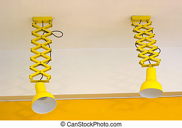 Two yellow lamp hanging from the ceiling