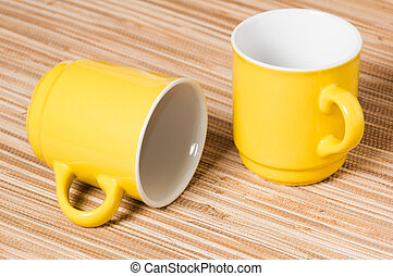 Two yellow mugs on a table, a close up
