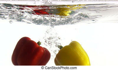 Two yellow red sweet bell peppers falls into clear water on white background