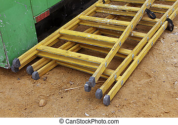 Two yellow wooden ladders at the construction site