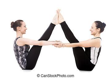 Smiling sporty yogi twin sisters doing fitness training, yoga asana in pair Ubhaya Padangusthasana (Both Feet Big Toe Posture or Balancing Stick Pose), isolated on white background