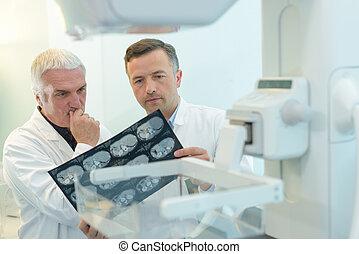 two yound doctors examining a x-ray film at the diaphanoscope