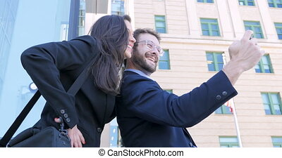Two young 30s coworkers take a selfie outside skyscrapers with an American flag