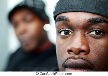 Two young African Americans. A person can be seen in the background out of focus