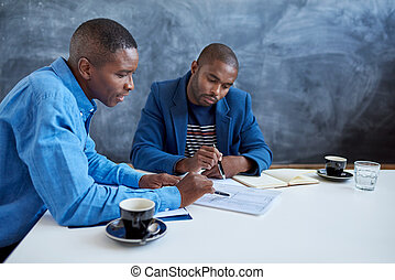 Two young African businessmen at work in an office