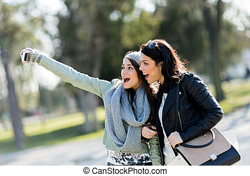 Two young and beautiful women taking a selfie of themselves on a sunny day