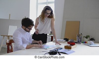 Two young architects consulting a project together.