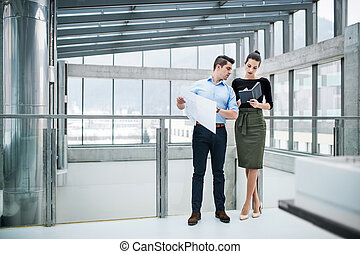 Two young architects with blueprints standing in office, talking.