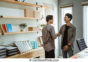 two young Asian business people shook their hands in agreement plan at work
