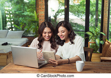 Two young asian female colleagues in office