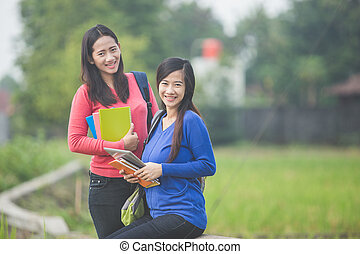 Two young Asian students holding books, smiling brightly to the camera