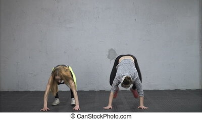 athletic women performing burpee exercise
