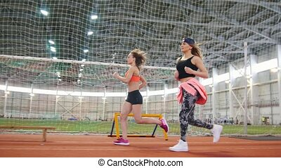 Two young athletic women running in sports arena indoors....
