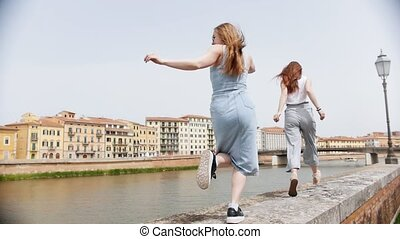 Two young attractive women run and dancing along the curb by...