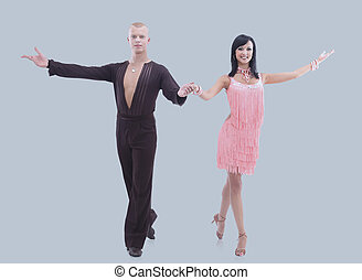 Two young ballroom dancers in studio  against  gray background