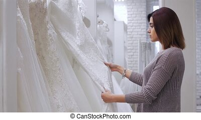 Two young beautiful brides trying her dress in shop. Wedding concept.
