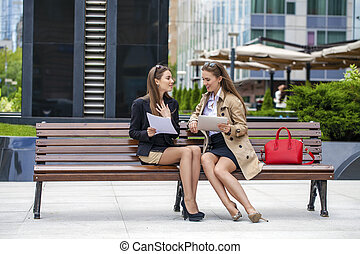 Two young beautiful business women sitting on a bench