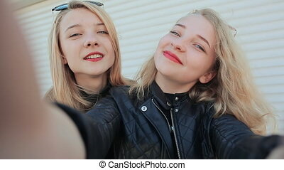 Two young beautiful girlfriends blonde fun and coquettish posing in front of the camera. Do selfie. Spring.