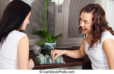 Two young beautiful girlfriends play chess at home