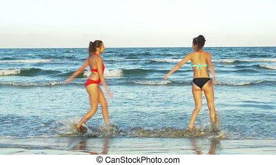 Two young beautiful girlfriends playing in the water