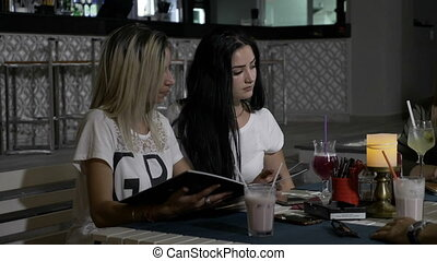 Two young beautiful girls in club sitting at a restaurant...