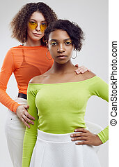 Two young beautiful hipster girls in colorful summer clothes