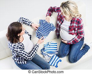 Two young beautiful pregnant women on a sofa
