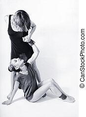 Two young beautiful women dancing