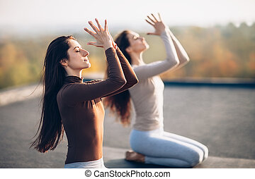 Two young beautiful women doing yoga asana on the roof...