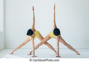 Two young beautiful women doing yoga asana revolved triangle pose