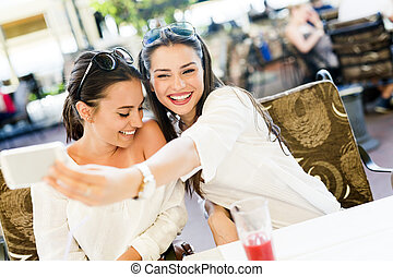 Two young beautiful women taking a selfie of themselves