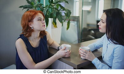 Two young beautiful women talk over cup of coffee in office.