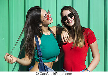 Two young best female friends standing by the green wall