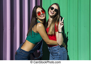 Two young best female friends standing by the wall