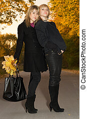 Two young blondes with autumn leaves on a road