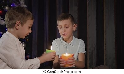 Two young boys hold in their hands inflamed decorative candles and show each other how they burn. Green and orange christmas candles
